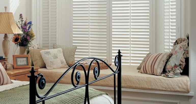 White shutters in a white bedroom bay window.