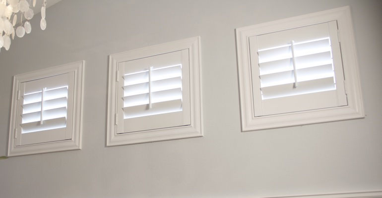 Shutters on three small square windows in laundry room