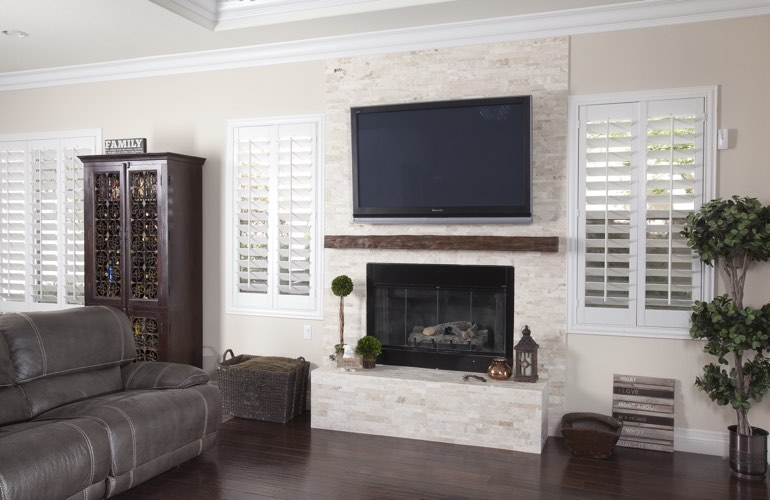 White plantation shutters in a Cleveland living room with dark hardwood floors.