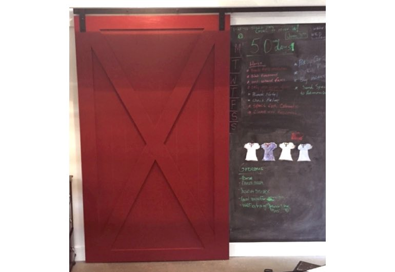 Red x-frame barn door with black hardware next to chalkboard 🚪