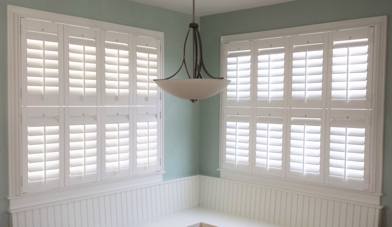 Pastel green wall in Cleveland kitchen with shutters.