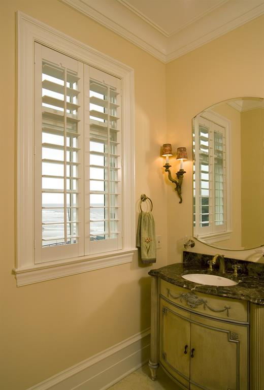 Plantation shutters in a light bathroom looking out over ocean