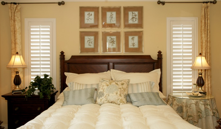Bedroom with two tall plantation shutters on either side of bed in Cleveland
