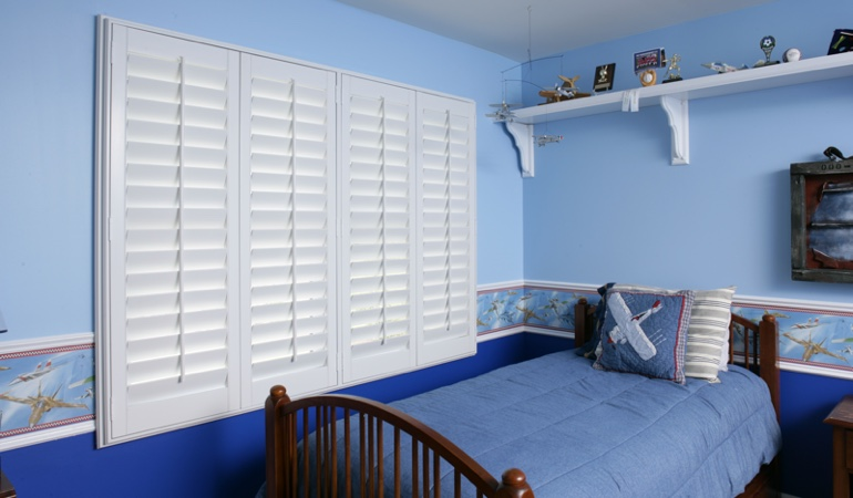 Blue kids bedroom with white plantation shutters in Cleveland